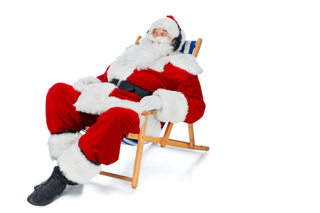 santa claus listening music with headphones while resting on beach chair on white
