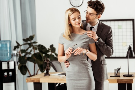 young lawyers flirting during work day in office, office romance concept