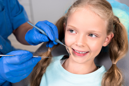 cropped shot of dentist with tools examining teeth of happy little child Stock Photo