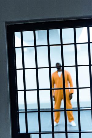 african american prisoner standing behind prison bars