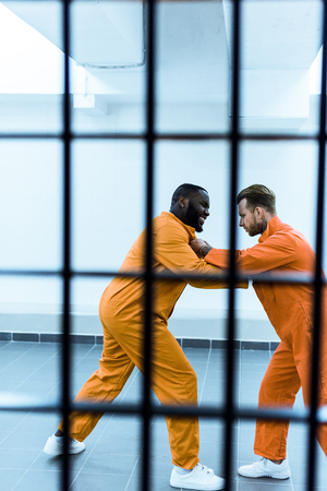 side view of multicultural prisoners threatening each other behind prison bars Foto de archivo - 111785110