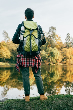 Rear view of traveler with backpack on autumnal background