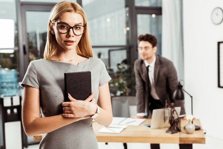 Selective focus of young female lawyer with notebook looking at camera while colleague standing at workplace in office Zdjęcie Seryjne