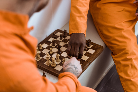 Cropped image of multicultural prisoners playing chess Stock Photo