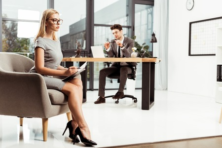 Young businesswoman with notebook sitting in armchair with colleague at workplace in office Zdjęcie Seryjne