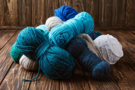 Close up view of white, blue and green yarn for knitting on wooden surface Stockfoto