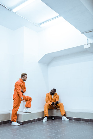 Multiethnic prisoners in light modern prison cell Stock Photo