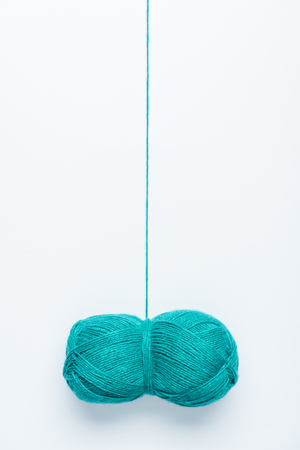 top view of blue yarn ball for knitiing on white backdrop