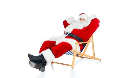 Happy Santa Claus relaxing on beach chair on white Stock Photo
