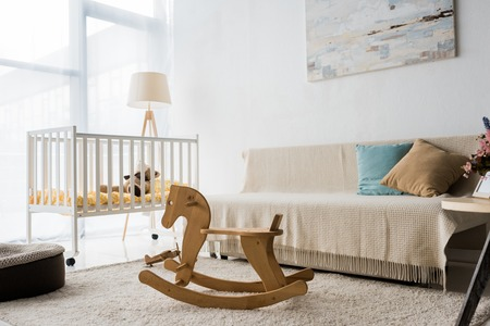 Modern interior design of nursery room with crib and rocking horse chair Standard-Bild - 112345739