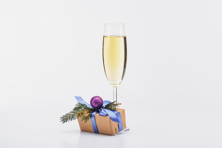 close up view of glass of champagne and christmas gift on white background