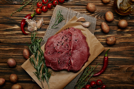 flat lay with raw meat on baking paper with vegetables and rosemary on wooden background Stock Photo