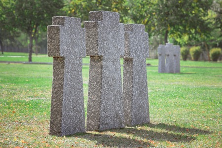 close up view of identical old gravestones placed in row on grass at cemetery
