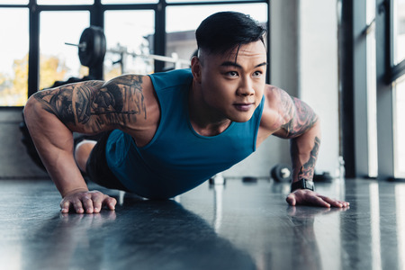 concentrated young asian sportsman doing plank exercise at gym