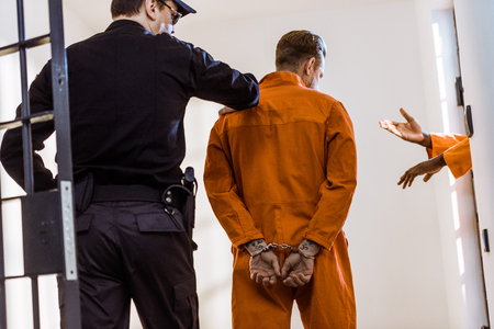 back view of prison guard leading criminal in handcuffs Stock Photo