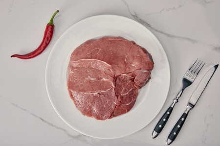 top view of fresh raw meat on plate with kitchen cutlery and chilli pepper on white background