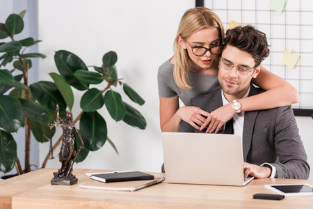 portrait of female lawyer hugging colleague at workplace with laptop in office, flirt and office romance concept Zdjęcie Seryjne
