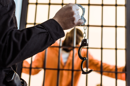 cropped image of prison guard showing handcuffs to african american prisoner Banco de Imagens