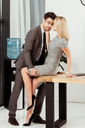 Vista lateral de jóvenes colegas coqueteando en el lugar de trabajo en la oficina, concepto de romance ofirce Foto de archivo
