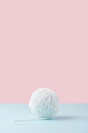 close up view of white yarn ball on blue and pink background