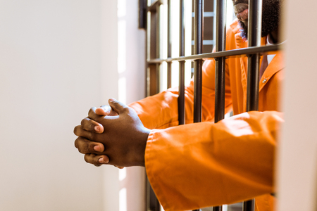 Cropped image of African american prisoner with hands in prison bars Foto de archivo - 112345748