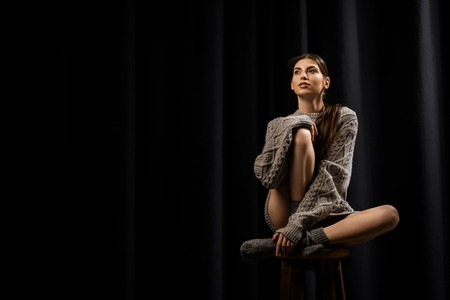 Beautiful pensive woman in woolen grey sweater and socks on black background