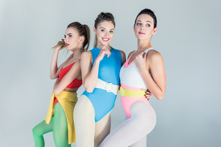 Beautiful young spotty women in colorful sportswear posing together isolated on grey