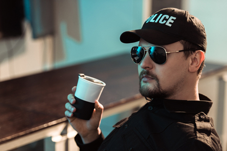 Prison guard holding cup of coffee