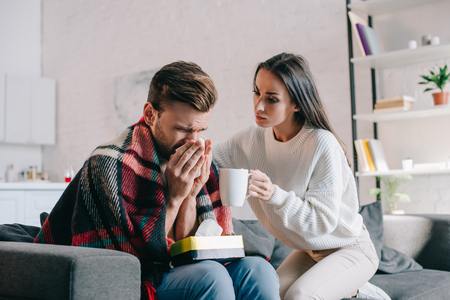 beautiful young woman holding cup of warming drink for sick boyfriend while he sneezing