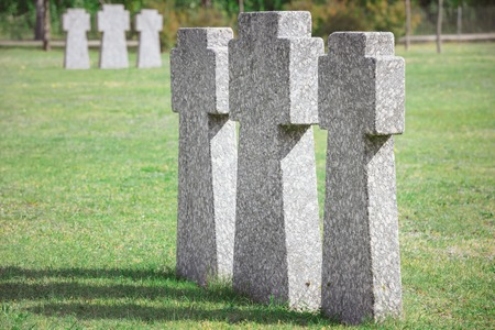 identical old memorial headstones placed in row at graveyard