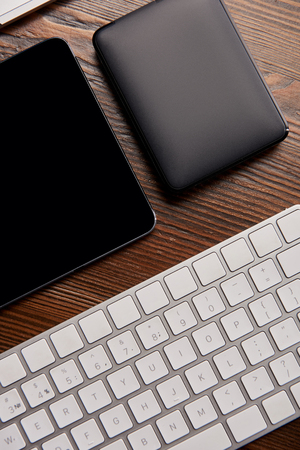 top view of wireless keyboard with digital tablet and portable hdd on wooden table