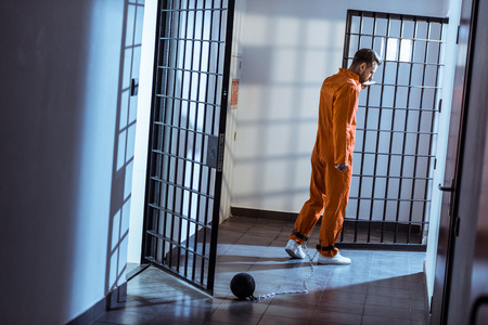 prisoner walking in corridor with weight tethered to leg