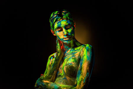 portrait of beautiful woman with colorful ultraviolet paints on body on black backdrop 版權商用圖片