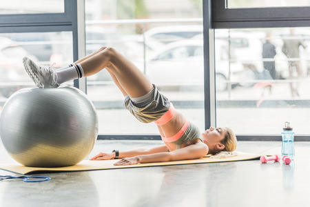 side view of young female athlete doing exercise with fitness ball at gym Stockfoto