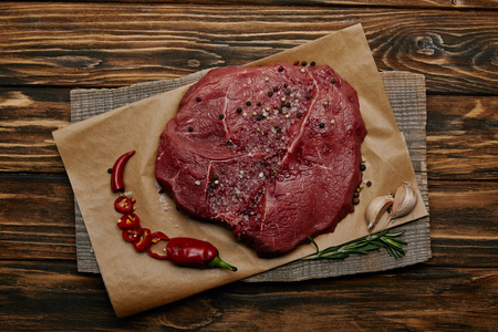 Top view of fresh raw meat on baking paper with chopped chili pepper and garlic on wooden background