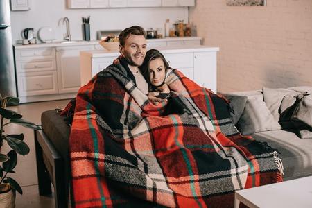 Feliz pareja joven relajándose en el sofá y viendo la televisión juntos mientras se cubren con cuadros