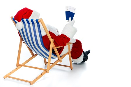Rear view of Santa Claus holding two passports and air tickets for Christmas trip while sitting in beach chair isolated on white 免版税图像