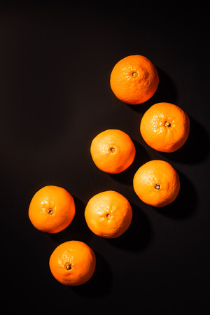 Top view of arrangement of wholesome tangerines on black background