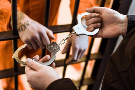 Przycięty obraz funkcjonariusza więziennego noszącego kajdanki na więźnia