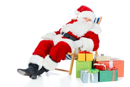 Santa Claus relaxing on beach chair with Christmas presents on white