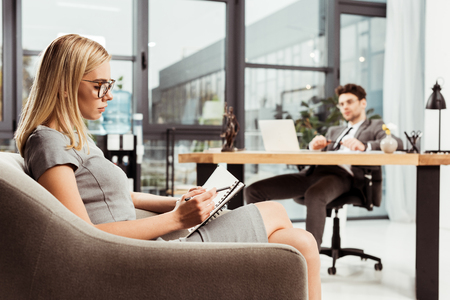 Businesswoman making notes in notebook while sitting in armchair with colleague at workplace in office
