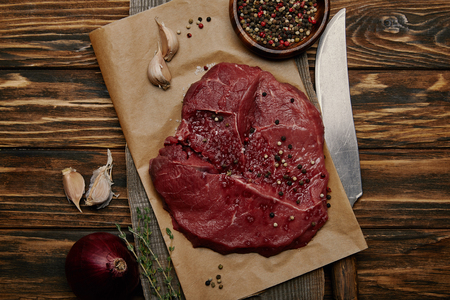 Flat lay with fresh raw meat on baking paper with garlic and spices on wooden background Stock Photo