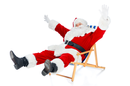 Excited Santa Claus gesturing and sitting on beach chair on white