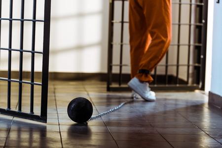 Cropped image of prisoner walking in orange uniform with weight tethered to leg Stok Fotoğraf