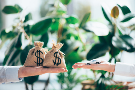 cropped shot of people exchanging sackcloth bags with dollar sign and car model Stock Photo