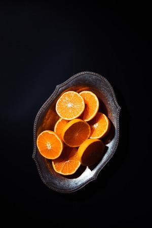 top view of cut mandarins halves in metal bowl on black tabletop Stock Photo