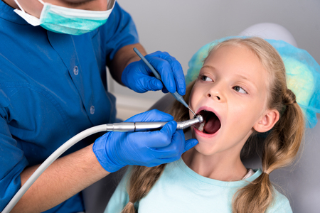 dentist with dental handpiece working with teeth of little kid