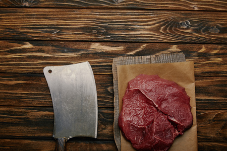 top view of raw meat on baking paper with butcher knife on wooden background