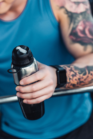 cropped view of tattooed sportsman holding metallic bottle of water