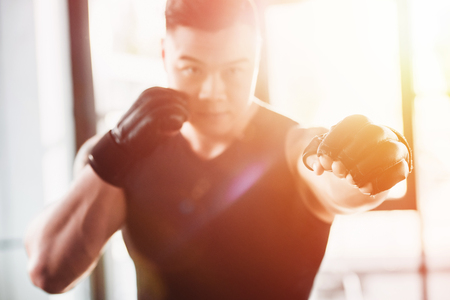 young sportsman wearing boxing gloves in sunlight Stock Photo